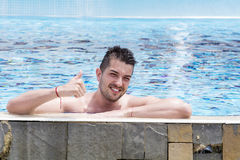 Portrait of young man in a pool.Thumbs up Royalty Free Stock Images