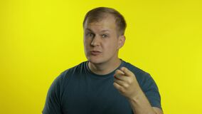 Portrait of young man posing in green t-shirt. Angry dissatisfied guy quarrels, waves his hands