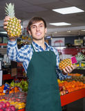 Portrait of young man posing in grocery. Portrait of young male posing with ananas in grocery and smiling Stock Photo