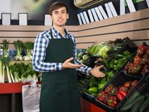 Portrait of young man posing in grocery. Portrait of positive young male posing in grocery and smiling Royalty Free Stock Image