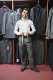 Portrait of young man posing with suits hanging in background Royalty Free Stock Image