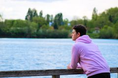 Portrait of a young man in profile in front of a lake and a forest royalty free stock images