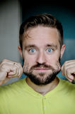 Portrait of young man pulling his beard. With surprised face Stock Image