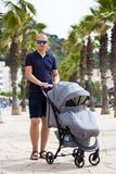 Portrait of young man pushing baby stroller royalty free stock images