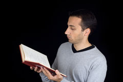 Portrait of a young man reading a book. On black background Stock Photos
