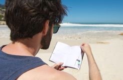 Portrait of a young man reading book at the beach Stock Photo