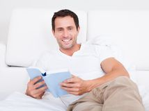 Portrait Of Young Man Reading Book On Bed Stock Photo