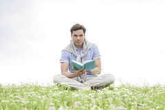 Portrait of young man reading book while sitting on grass against sky Royalty Free Stock Photography