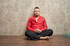 Portrait of a young man, in red shirt and black slacks, hairstyl. E with shaved temples and slicked back hair at the head, different emotions, wood floor, beard Royalty Free Stock Photos