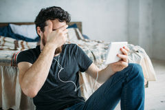 Portrait of a young man relaxing and watching a TV show on a tablet computer. Bearded guy in earphones closing his face with one hand because of bad scene on Royalty Free Stock Image