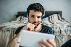 Portrait of a young man relaxing and watching a TV show on a tablet computer Royalty Free Stock Photography