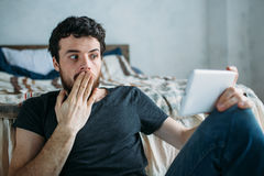 Portrait of a young man relaxing and watching a TV show on a tablet computer. Portrait of a happy young man relaxing and watching a TV show on a tablet computer Stock Photos