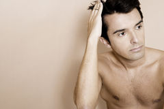 Portrait of a young man running his fingers through his hair royalty free stock images