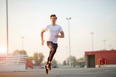 Young man running in urban area royalty free stock image