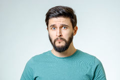 Portrait of young man with sad face expression. On gray background stock photo