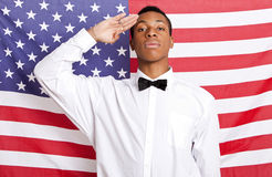 Portrait of young man saluting against American flag Stock Photos