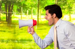 Portrait of a young man screaming with a megaphone, in a blurred green background Stock Image