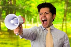 Portrait of a young man screaming with a megaphone, in a blurred green background Stock Photos