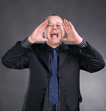 Portrait of a young man screaming out loud. On a gray background royalty free stock photography