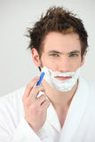 Portrait of a young man shaving. Young man shaving on white background royalty free stock photos