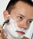 Portrait of a young man shaving his beard. With razor Royalty Free Stock Image