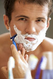 Portrait of young man shaving Stock Photos