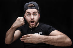 Portrait of young man in shirt and cap on black background makes the hand trick Royalty Free Stock Images
