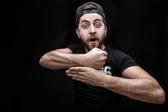 Portrait of young man in shirt and cap on black background makes the hand trick Royalty Free Stock Photography