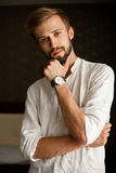 Portrait of young man in shirt with wristwatch on hand. royalty free stock photos