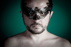 Portrait of young man shirtless with mask against dark backgroun Royalty Free Stock Photography
