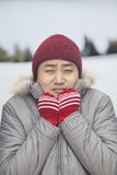 Portrait of young man shivering in cold temperature in big coat Royalty Free Stock Photos