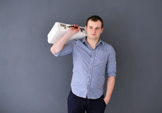 Portrait of a young man with shoulder bag isolated on gray background Stock Photo