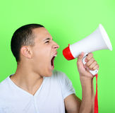 Portrait of young man shouting with a megaphone against green ba Royalty Free Stock Photography