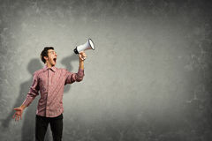 Portrait of a young man shouting using megaphone. Behind the concrete wall Stock Images