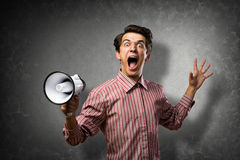 Portrait of a young man shouting using megaphone. Behind the concrete wall Stock Photography