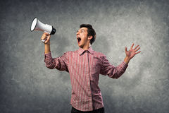 Portrait of a young man shouting using megaphone. Behind the concrete wall Stock Photo