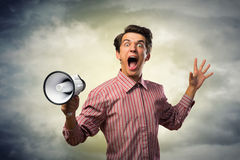 Portrait of a young man shouting using megaphone. Behind the dark clouds Stock Photos
