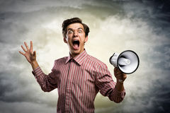 Portrait of a young man shouting using megaphone. Behind the dark clouds Stock Images