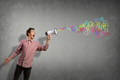 Portrait of a young man shouting using megaphone. Of the horn fly, abstract symbols Stock Photography