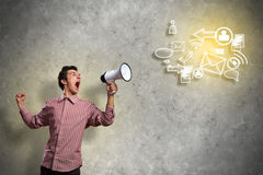 Portrait of a young man shouting using megaphone. Of the horn fly, abstract symbols Royalty Free Stock Image