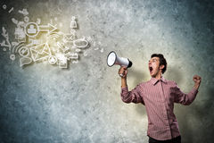 Portrait of a young man shouting using megaphone. Of the horn fly, abstract symbols Stock Images