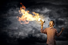 Portrait of a young man shouting using megaphone. Of the horn fly fire Stock Photo