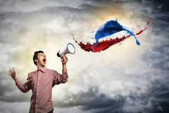 Portrait of a young man shouting using megaphone. Of the horn fly, splashes of paint Stock Image