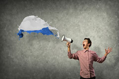 Portrait of a young man shouting using megaphone. Of the horn fly, splashes of paint Royalty Free Stock Images