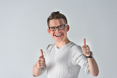 Portrait of young man showing LIKE gesture. Portrait of a smiling casual spectacled man showing two thumbs up and looking at camera over gray background. Man Royalty Free Stock Photo