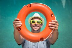 Tourist guy holding lifebuoy against blue swimming pool water su. Portrait of young man showing and looking through lifebuoy outdoors. Tourism and summer Stock Image