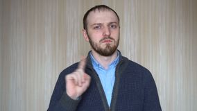 Portrait of Young Man showing stop sign, Dislike, Rejecting Gesture, Disagree Sign, Shaking Finger.  stock footage