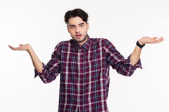 Portrait of a young man shrugging shoulders Stock Image