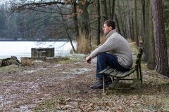 Portrait of young man sit on old bench with icy pond in sweater from side.  royalty free stock photos