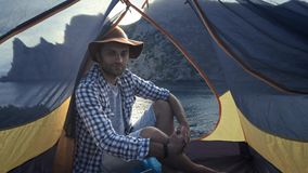 PORTRAIT: A young man sits in a camping tent. Enjoys a beautiful view of the sea and mountains. Hiking adventure in the stock footage